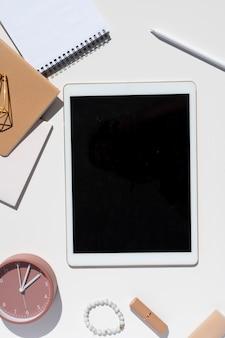 Weiß-gold-tablet-pc mit stiftmodell. femininer stilvoller schreibtisch. vertikales modell der draufsicht.