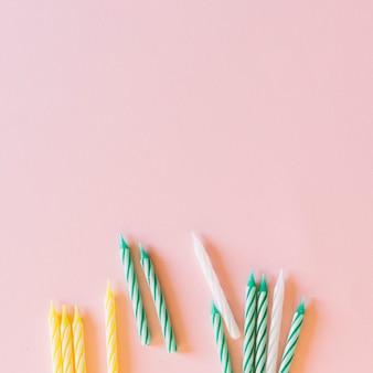 Weiß; grüne und gelbe streifenmusterkerzen auf rosa hintergrund