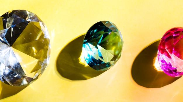 Weiß; grüner und rosafarbener kristalldiamant auf gelbem hintergrund
