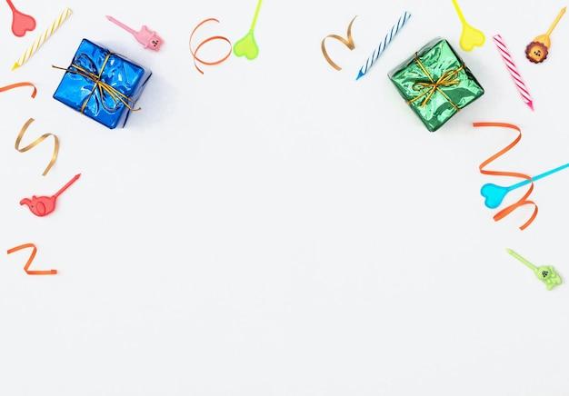 Weiß mit eingewickelten geschenkboxen, luftschlangen, kerzen und spießen.