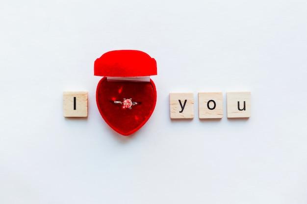 Weiß mit hölzernen wörtern ich liebe dich und diamantverlobungsring in der roten geschenkbox.