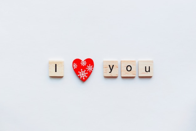 Weiß mit hölzernen wörtern ich liebe dich und rotes herz, symbol der liebe.