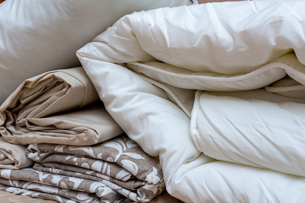 Weiß und beige verpackter stapel der leinenbettwäschedecke mit kissen- und bettwäscheblättern