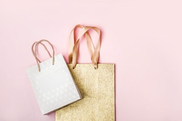 Weiß- und goldpakete auf rosa hintergrund. ferienverkaufskonzept in pastellfarben.