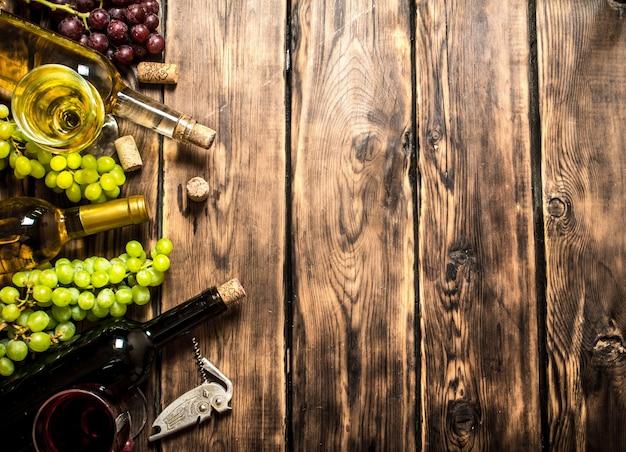 Weiß- und rotwein mit traubenzweigen, korkenzieher und korken auf einem holztisch