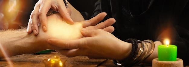 Weissagung durch die linien der hand. ein wahrsager oder orakel hält eine handfläche in den händen und sagt das schicksal voraus