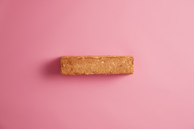 Weißbrot-toast mit appetitlicher kruste, die von oben fotografiert wird, lokalisiert über rosigem hintergrund. scheibe getreidebrot. leckeres leckeres frühstück. snack und essen. richtiges substanzielles ernährungskonzept