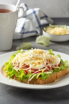 Weißbrotsandwich mit kopfsalat, tomate, gekochtem ei und geriebenem käse.