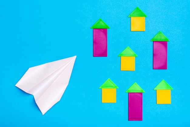 Weißbuch flugzeug fliegt über farbige figuren von häusern auf blauem karton. ansicht von oben. flugzeugabsturzgefahr konzept