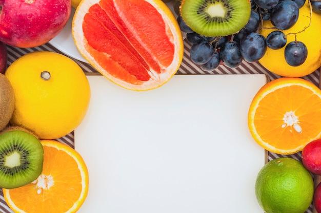 Weißbuch mit bunten zitrusfrüchten; trauben und kiwi