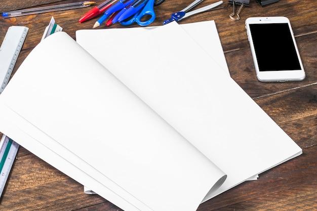 Weißbuch mit schreibwaren und smartphone auf holztisch