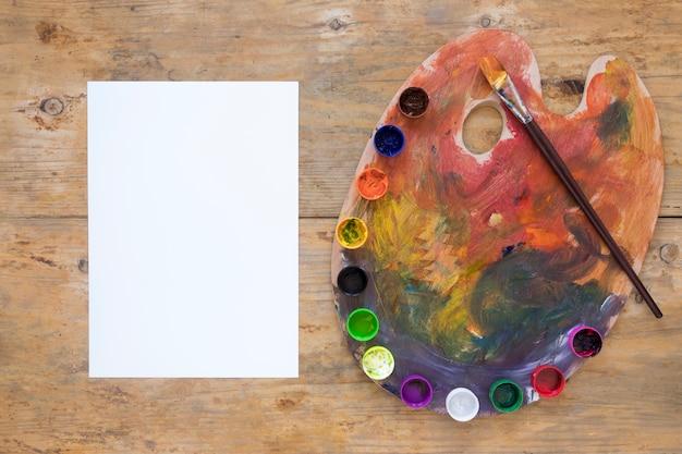 Weißbuch und gouache auf palette mit pinsel platziert