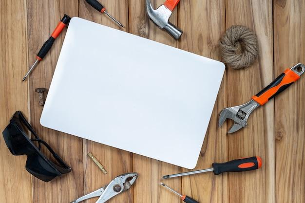 Weißbuch und manueller werkzeugsatz auf bretterboden.