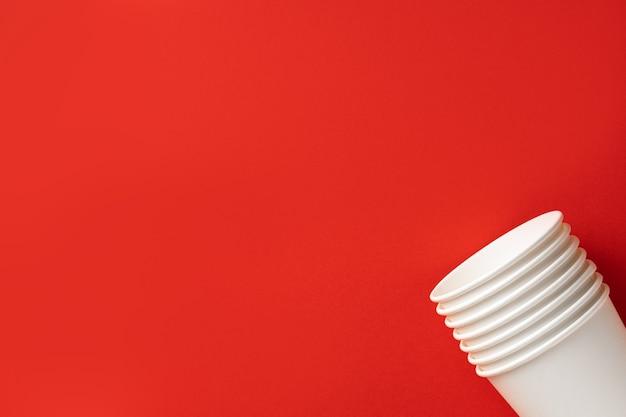 Weißbuchbecher auf rotem grund. ansicht von oben.platz für text.ökologiekonzept