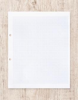 Weißbuchblatt mit gitterlinie muster auf holz.