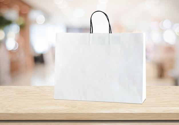 Weißbucheinkaufstasche, die auf hölzerner tabelle über unscharfem speicher mit kopienraum steht