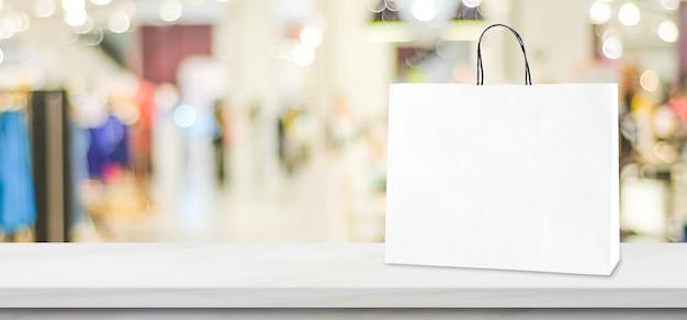 Weißbucheinkaufstasche, die auf weißer marmortabelle über unscharfem speicherhintergrund steht