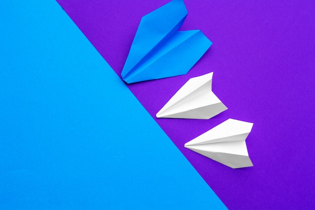 Weißbuchflugzeug auf einem blauen und purpurroten papier