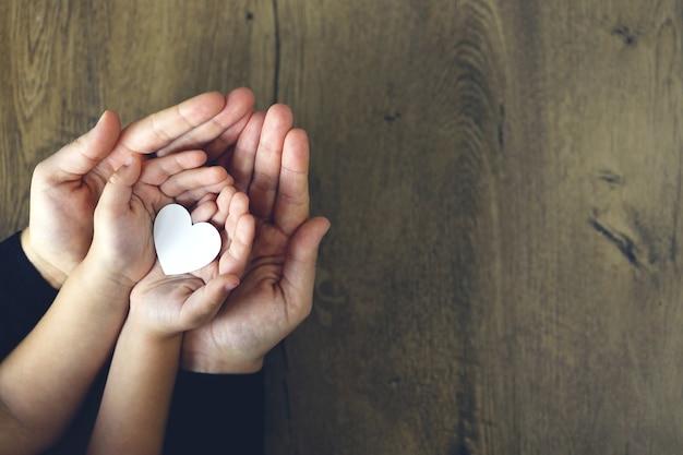 Weißbuchherz in den palmen des kindes und der frau, draufsicht. liebe, muttertag, familienkonzept.