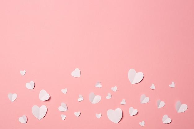Weißbuchherzen auf einem rosa hintergrund. zusammensetzung des valentinstags. banner. flache lage, draufsicht.
