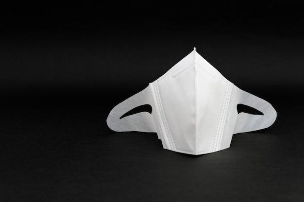 Weiße 3d-gesichtsmaske zum schutz vor covid 19 auf schwarzem hintergrund isoliert