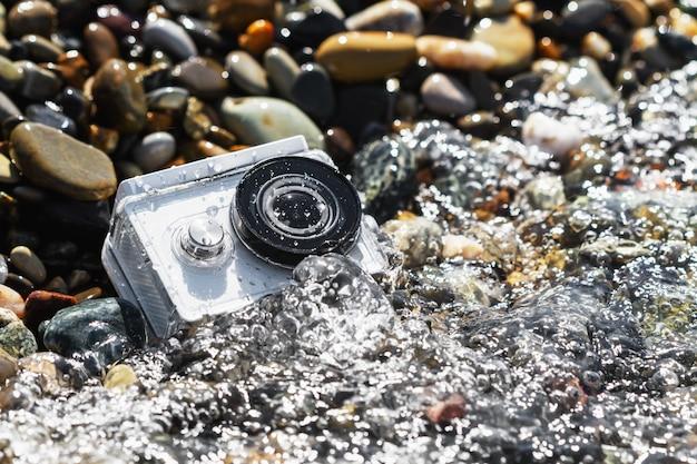 Weiße actionkamera mit unterwassergehäuse im wasser am kieselstrand