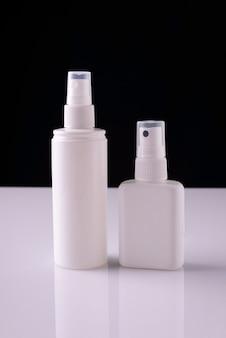 Weiße aerosolflaschen auf weißem tisch und schwarzem hintergrund