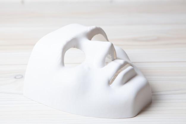 Weiße anonyme maske auf dem tisch
