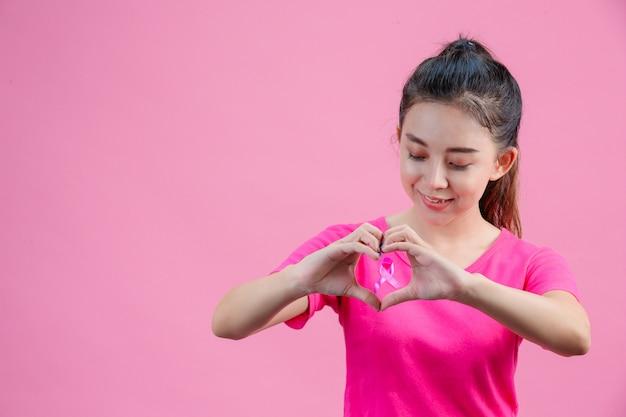 Weiße asiatische frau, die ein rosa hemd trägt handgemachte herzform auf einem rosa.