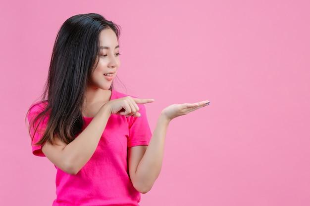 Weiße asiatische frau die rechte hand zeigte auf die linke hand, die die rechte hand hielt. auf einem rosa.