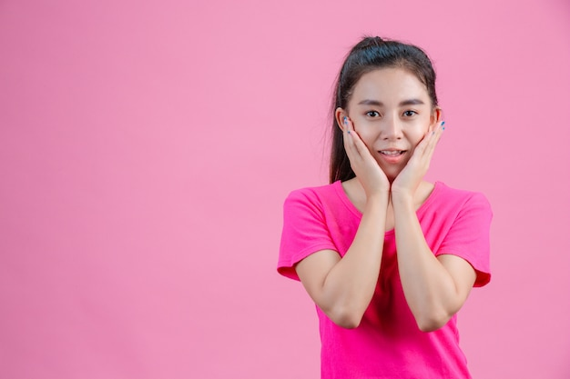 Weiße asiatische frauen tragen rosa hemden. mit beiden händen das gesicht auf dem rosa halten.