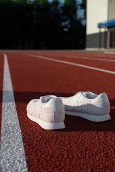 Weiße athletische turnschuhe auf einem stadionlaufband. konzepte von sport, gesundheit und wellness.