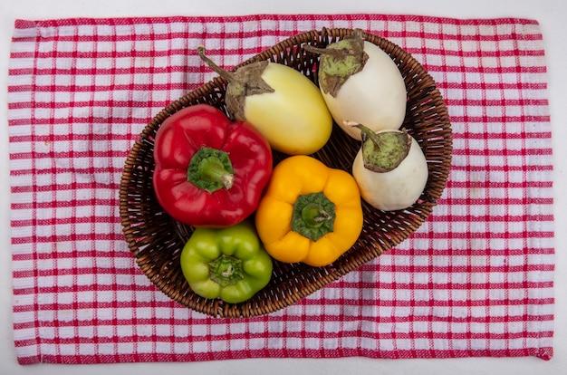 Weiße aubergine der draufsicht mit farbigen paprikaschoten in einem korb auf einem rot karierten handtuch