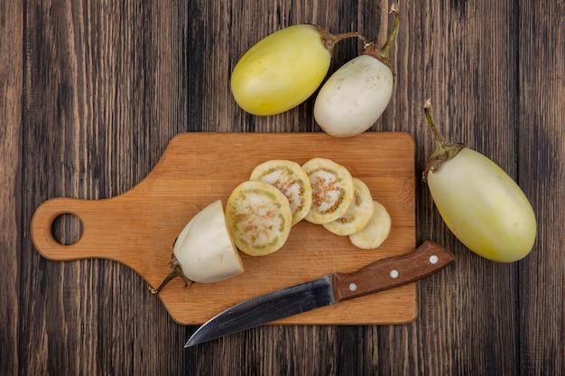 Weiße auberginenscheiben der draufsicht mit messer auf schneidebrett auf hölzernem hintergrund