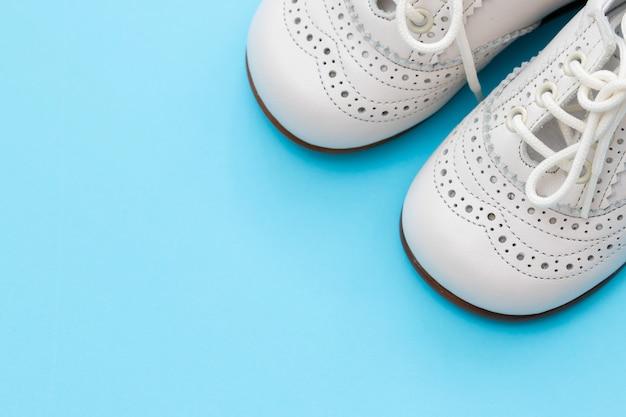 Weiße babyschuhe auf blauem hintergrund