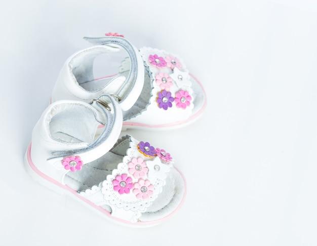 Weiße babyschuhe auf weißem hintergrund
