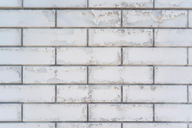 Weiße backsteinmauer mit abblätternder farbe. backsteinraum. nahansicht