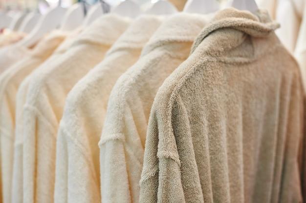 Weiße bademäntel, die im hölzernen wandschrank hängen