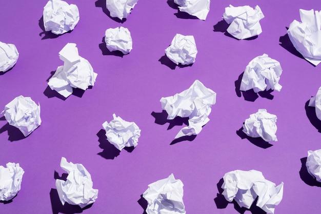 Weiße bälle aus zerknittertem papier auf dem boden liegend
