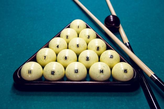 Weiße bälle für billard in einem dreieck und zwei queue und schwarze kugel