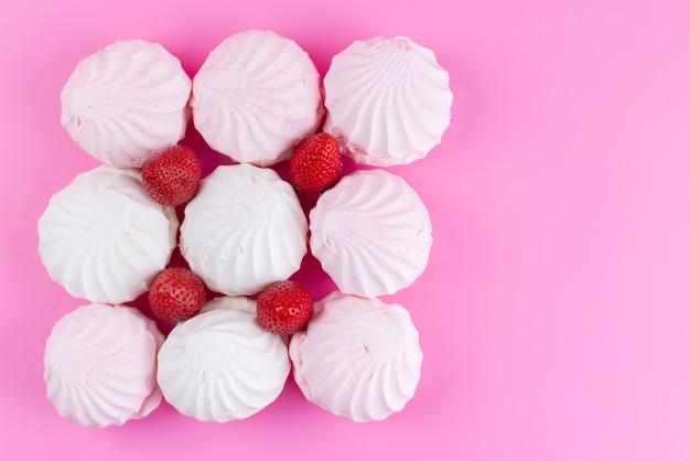 Weiße baiser der draufsicht mit frischen roten erdbeeren, die auf rosa schreibtisch, keks-süßwaren süßer zuckerfarbe ausgekleidet sind