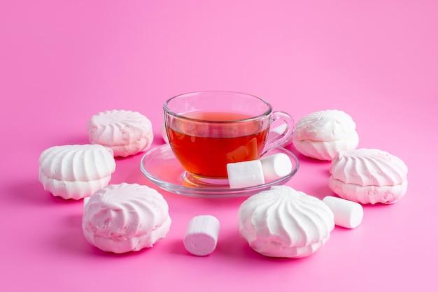 Weiße baiser der vorderansicht, die zusammen mit einer tasse tee köstlich sind