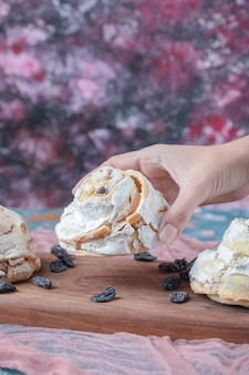 Weiße baiserplätzchen mit schwarzen rosinen auf einem holzbrett.