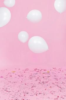 Weiße ballone in einer luft über dem konfetti gegen rosa hintergrund