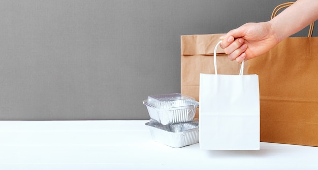 Weiße bastelpapiertüte in weiblicher hand. lebensmittelfolienbehälter und papierverpackungen auf grauem hintergrund des tisches. lebensmittel-lieferservice.