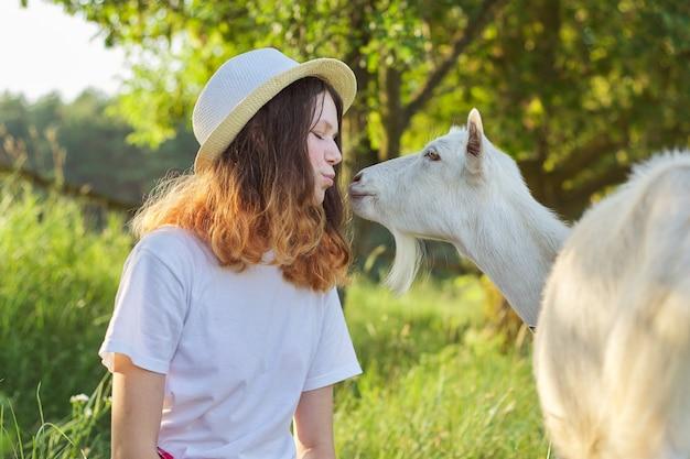 Weiße bauernziege, die teenager-mädchen küsst