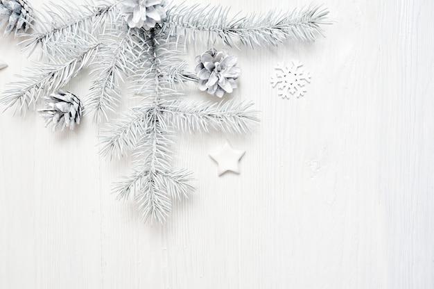 Weiße baumastgrenze des weihnachtsrahmens über weißem hölzernem