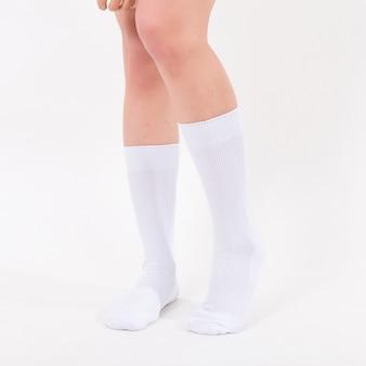 Weiße baumwollsocken an den füßen der schönen frau. isoliert auf weißem hintergrund.