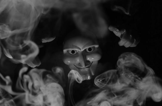 Weiße beängstigende maske auf schwarzem hintergrund mit weißen händen.