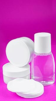 Weiße behälter mit kosmetika (gesichtscreme, handcreme, mineralwasser, wattepads) auf weißem rosa, vertikal angeordnet